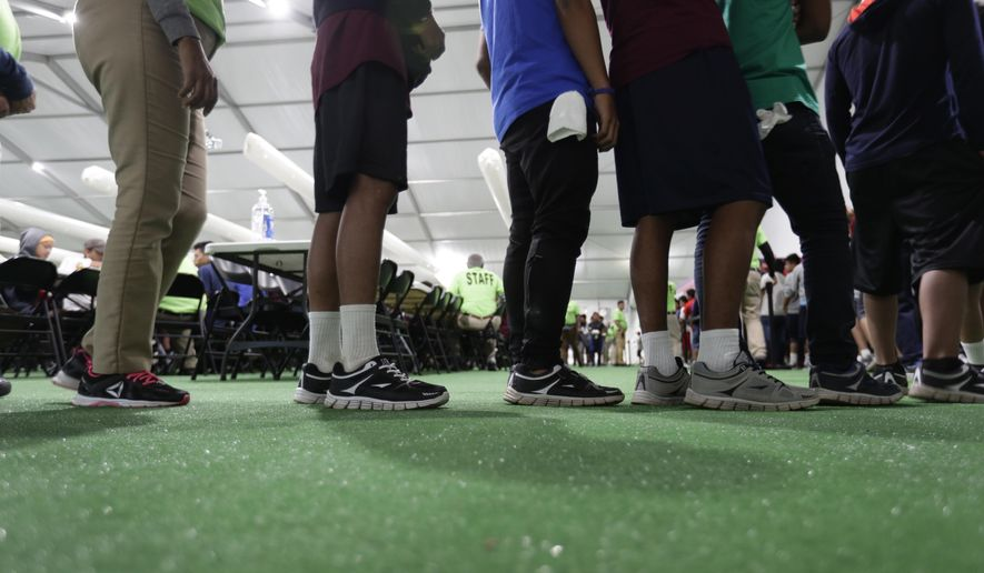 In this July 9, 2019, file photo, immigrants line up in the dining hall at the U.S. government's newest holding center for migrant children in Carrizo Springs, Texas. The government will be able to hold immigrant children detained at the Mexican border for a longer period of time under a move by the Trump administration (AP Photo/Eric Gay, File)