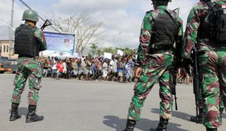 Indonesian soldiers stand guard during a protest in Timika, Papua province, Wednesday, Aug. 21, 2019. Indonesia has deployed over 1,000 security personnel to the restive province of West Papua amid spreading violent protests sparked by accusations that security forces had arrested and insulted Papuan students in East Java . (AP Photo/Jimmy Rahadat)