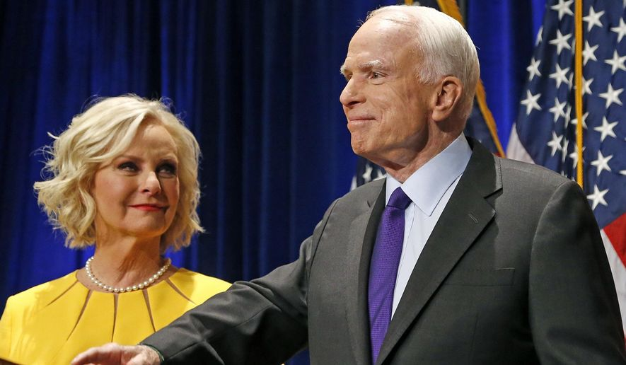 """In this Tuesday, Nov. 8, 2016, file photo, Sen. John McCain, R-Ariz., right, pauses as his wife, Cindy McCain, looks at him on stage after giving his victory speech as he announces his win over Democratic challenger Rep. Ann Kirkpatrick, in Phoenix. The family of the late Sen. John McCain says they want to build a library on land donated by Arizona State University to house his archives and provide a """"gathering place"""" for respectful dialogue. (AP Photo/Ross D. Franklin, File)"""