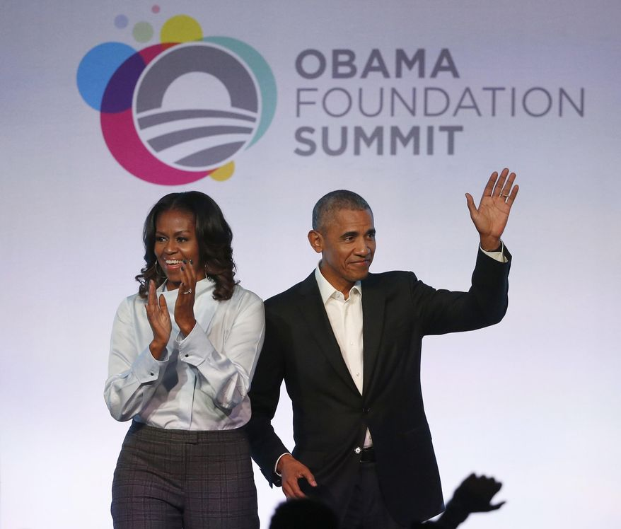FILE - In this Oct. 13, 2017 file photo, former President Barack Obama, right, and former first lady Michelle Obama arrive for the first session of the Obama Foundation Summit in Chicago. A documentary about an Ohio auto glass factory that is run by a Chinese investor debuted Wednesday, Aug. 21, 2019, on Netflix, as the streaming service's first project backed by Michelle and Barack Obama's new production company. (AP Photo/Charles Rex Arbogast, File)