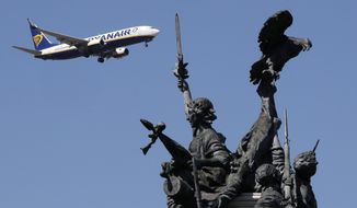 A Ryanair airplane approaching for landing at Lisbon airport flies past the Monument to the Heroes of the Peninsular War, in the foreground, Wednesday, Aug. 21 2019.  A strike by Portuguese cabin crew working for budget airline Ryanair is causing little impact, with only some minor delays reported Wednesday. (AP Photo/Armando Franca)
