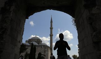 In this photo taken on Tuesday, Aug. 20, 2019, a man walks near Fatih mosque in Istanbul. Syrians say Turkey has been detaining and forcing some Syrian refugees to return back to their country the past month. The expulsions reflect increasing anti-refugee sentiment in Turkey, which opened its doors to millions of Syrians fleeing their country's civil war. (AP Photo/Lefteris Pitarakis)
