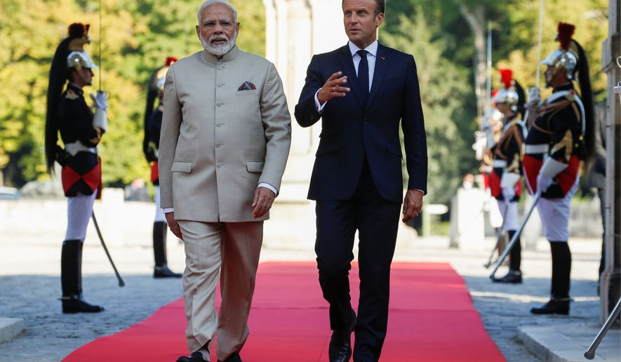 French President Emmanuel Macron (right) welcomes Indian Prime Minister Narendra Modi at the Chateau of Chantilly on Thursday. President Trump is to meet with Mr. Macron and discuss France's new tax on technology companies. (Associated Press)