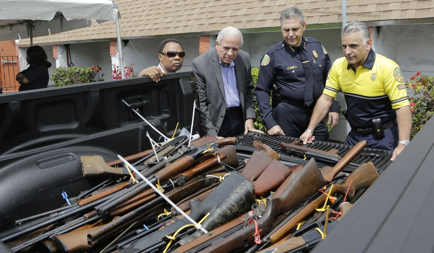 The Rev. Jerome Starling, left, Miami Mayor Tomas Regalado, second from left, Miami Police Chief Rodolfo Llanes, second from right, and Miami Assistant Police Chief Jorge Colina, right, look over rifles that were turned into Miami police during a gun buyback program held at the Jordan Grove Missionary Baptist Church, Saturday, March 12, 2016, in Miami. The event was organized by Starling in response to continuing gun violence in the city. Over 100 firearms were collected. (AP Photo/Lynne Sladky)