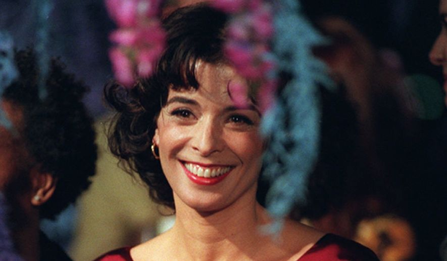 """Actress Annabella Sciorra, one of the stars of the new Polygram film, """"What Dreams May Come,"""" with Robin Williams and Cuba Gooding Jr., is photographed through floral decorations at the premiere of the film, Monday, Sept. 28, 1998, at the Academy of Motion Picture Arts & Sciences in Beverly Hills, Calif.  (AP Photo/Chris PIzzello) ** FILE **"""