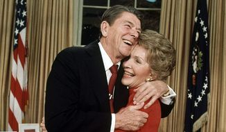 President Ronald Reagan embraces first lady Nancy Reagan Jan. 30, 1984 in Washington, after he announced that he will run for a second term as President. Reagan, 72, confirmed that Vice President George Bush will again be his running mate in a campaign already well underway. (AP Photo/Ira Schwarz)