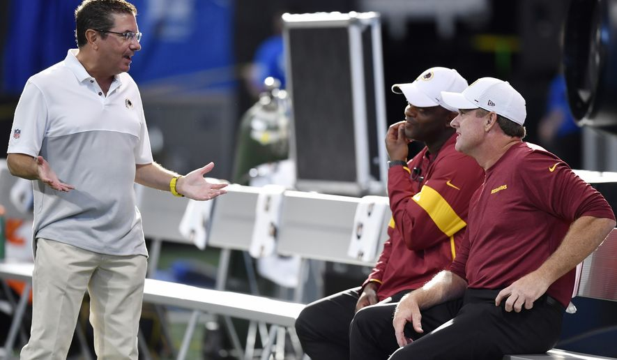 Washington Redskins owner Daniel Snyder, left, speaks with Washington Redskins head coach Jay Gruden, right, before the first half an NFL preseason football game against the Atlanta Falcons, Thursday, Aug. 22, 2019, in Atlanta. (AP Photo/Mike Stewart)