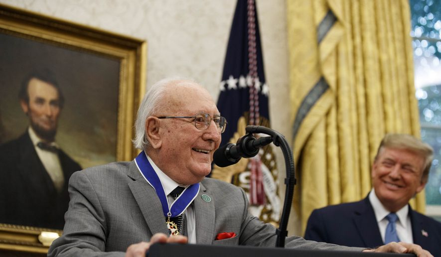 Former NBA basketball player and coach Bob Cousy, of the Boston Celtics, speaks as President Donald Trump smiles during a Presidential Medal of Freedom ceremony for Cousy, in the Oval Office of the White House, Thursday, Aug. 22, 2019, in Washington. (AP Photo/Alex Brandon)