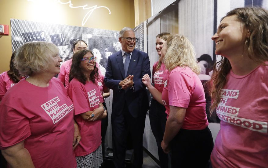 Gov. Jay Inslee talks with supporters of Planned Parenthood after speaking at a news conference addressing a change in rules on the nearly 50-year-old Title X family planning program, Thursday, Aug. 22, 2019, in Seattle. Planned Parenthood clinics in several states are charging new fees, tapping financial reserves, intensifying fundraising and warning of more unintended pregnancies and sexually transmitted diseases after its decision to quit a $260 million federal family planning program in an abortion dispute with the Trump administration. (AP Photo/Elaine Thompson)