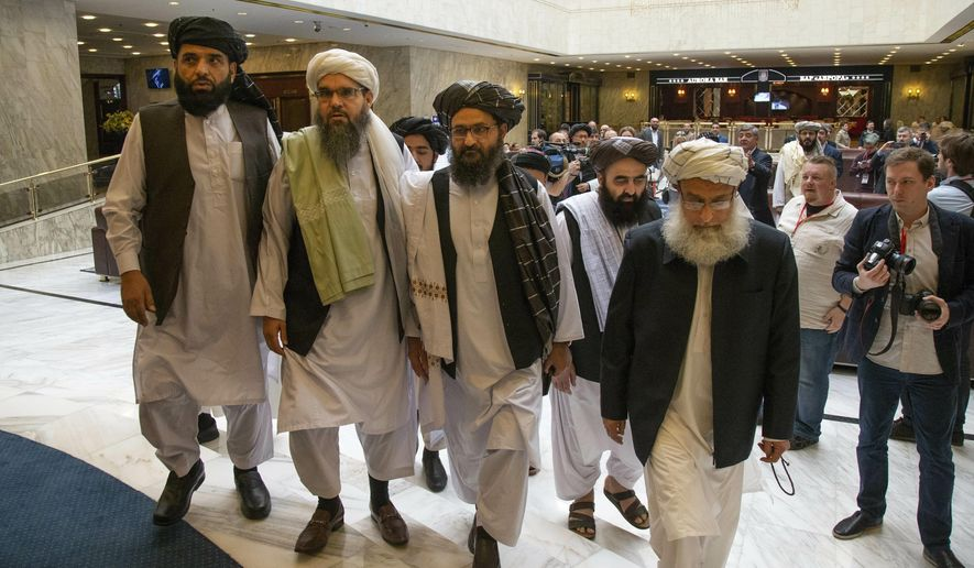 FILE - In this May 28, 2019 file photo, Mullah Abdul Ghani Baradar, the Taliban group's top political leader, third from left, arrives with other members of the Taliban delegation for talks in Moscow, Russia. U.S. envoy Zalmay Khalilzad and the Taliban have resumed negotiations on ending America's longest war. A Taliban member said Khalilzad also had a one-on-one meeting on Wednesday, Aug. 21, 2019, with  Baradar, the Taliban's lead negotiator, in Qatar, where the insurgent group has a political office. (AP Photo/Alexander Zemlianichenko, File)