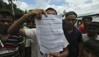 A Rohingya refugee displays to journalists a demand letter about Rohingya repatriation at Nayapara camp in Cox's Bazar, Bangladesh, Thursday, Aug.22, 2019. Bangladesh's refugee commissioner said Thursday that no Rohingya Muslims turned up to return to Myanmar from camps in the South Asian nation. (AP Photo/Mahmud Hossain Opu)