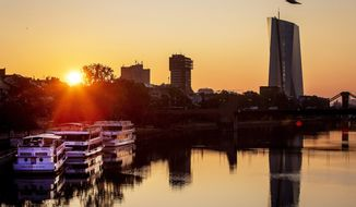 The sun rises next to the European Central Bank at the river Main in Frankfurt, Germany, early Thursday, Aug. 22, 2019. (AP Photo/Michael Probst)