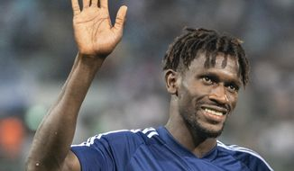 FILE - In this Aug. 11, 2019 file photo Hamurg's Bakery Jatta waves to fans after a match of Chemnitz against Hamburg in Chemnitz, Germany. Hamburger SV has reinforced its support for midfielder Bakéry Jatta as the dispute over his identity continues to inflame tempers in Germany's second division. The affair began with a report by Sport Bild magazine suggesting that Jatta – who became the first refugee to play in the Bundesliga when he made his debut for Hamburg in April 2017 – has been playing under a false name and is in fact two years older than he claims to be. (Robert Michael/dpa via AP)