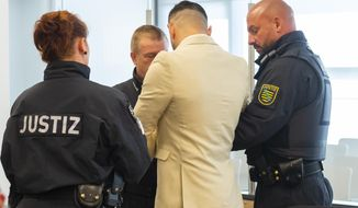 The  defendant Alaa S. arrives at the court in Dresden, Germany, Thursday, Aug. 22, 2019. A German court has convicted a Syrian asylum-seeker over a fatal stabbing in the city of Chemnitz last year that touched off far-right protests. The state court in Dresden convicted Alaa S. of manslaughter and dangerous bodily harm in the killing last August of Daniel Hillig. (Matthias Rietschel/dpa via AP)