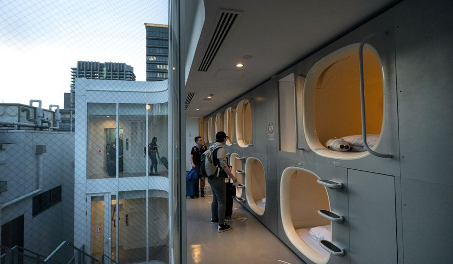 In this May 30, 2019, photo, a group of American tourists walk toward their pods after checking in at 9H capsule hotel at Chiyoda district of Tokyo. Tokyo is shaping up as a very pricey Olympics. Ticket demand is unprecedented, so scalping is sure to flourish. Hotel rates are soaring to five-six times normal. And getting here will be costly, particularly for fans from the Americas and Europe. (AP Photo/Jae C. Hong)