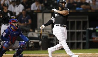 Chicago White Sox's Yoan Moncada watches his two-run home run next to Texas Rangers catcher Jose Trevino during the third inning of a baseball game Thursday, Aug. 22, 2019, in Chicago. (AP Photo/Jeff Haynes)