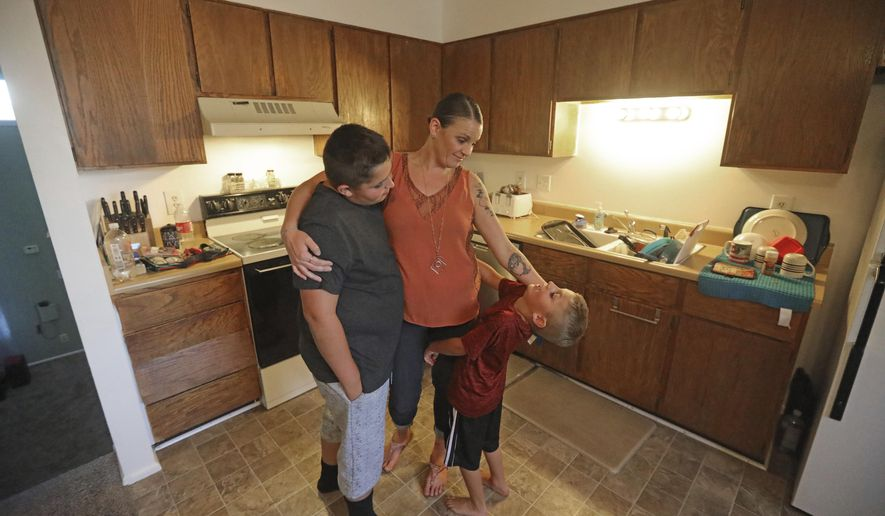 Misty Dotson hugs her son's at their home Tuesday, Aug. 20, 2019, in Murray, Utah. Dotson is a 33-year-old single mother of two boys, ages 12 and 6, who goes to Planned Parenthood for care through the Title X program. Dotson is among the 39,000 people received treatment from Planned Parenthood of Utah in 2018 under a federal family planning program called Title X. The organization this week announced it is pulling out program rather than abide by a new Trump administration rule prohibiting clinics from referring women for abortions. (AP Photo/Rick Bowmer)