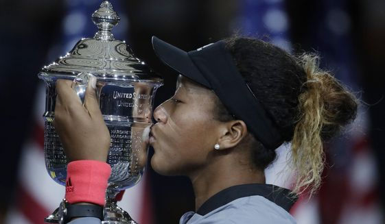 FILE - In this Sept. 8, 2018, file photo, Naomi Osaka, of Japan, kisses the trophy after defeating Naomi Osaka, of Japan, in the women's final of the U.S. Open tennis tournament in New York. Osaka is ranked No. 1 heading into the U.S. Open, where she will attempt to defend a Grand Slam title for the first time. (AP Photo/Julio Cortez, File)