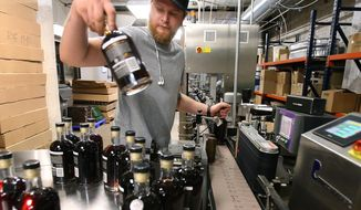 In this Thursday, June 6, 2019 photo, Zach Colyer checks the labels on bottles as they come off the production line at Balcones Distilling in Waco, Texas. More Texas farmers are wading into the whiskey business, but their end users are far removed from the era of moonshine stills and midnight raids by ax-toting lawmen. (Jerry Larson/Waco Tribune-Herald via AP)