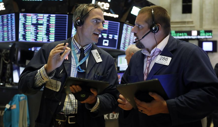FILE - In this Aug. 19, 2019, file photo traders Gregory Rowe, left, and Michael Milano work on the floor of the New York Stock Exchange. The U.S. stock market opens at 9:30 a.m. EDT on Friday, Aug. 23. (AP Photo/Richard Drew, File)