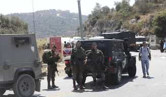 Israeli soldiers secure an area near Dolev settlement in the West Bank, Friday, Aug. 23, 2019, after three Israelis were wounded in an explosion. The Israeli military said it suspects the explosion near Dolev settlement, northwest Jerusalem, to be a Palestinian attack. (AP Photo/Mahmoud Illean)
