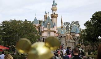 In this Jan. 22, 2015, file photo, visitors walk toward Sleeping Beauty's Castle in the background at Disneyland Resort in Anaheim, Calif. (AP Photo/Jae C. Hong, File)