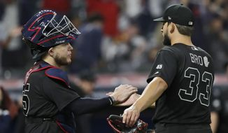 Cleveland Indians relief pitcher Brad Hand, right, is congratulated by Roberto Perez after they defeated the Kansas City Royals in a baseball game Friday, Aug. 23, 2019, in Cleveland. (AP Photo/Tony Dejak)