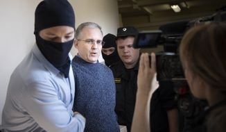 Paul Whelan, a former U.S. Marine, second left, who was arrested for alleged spying in Moscow at the end of 2018, speaks to a journalist as he escorted by Federal Security Service officers to a courtroom in Moscow, Russia, Friday, Aug. 23, 2019. (AP Photo/Alexander Zemlianichenko) ** FILE **