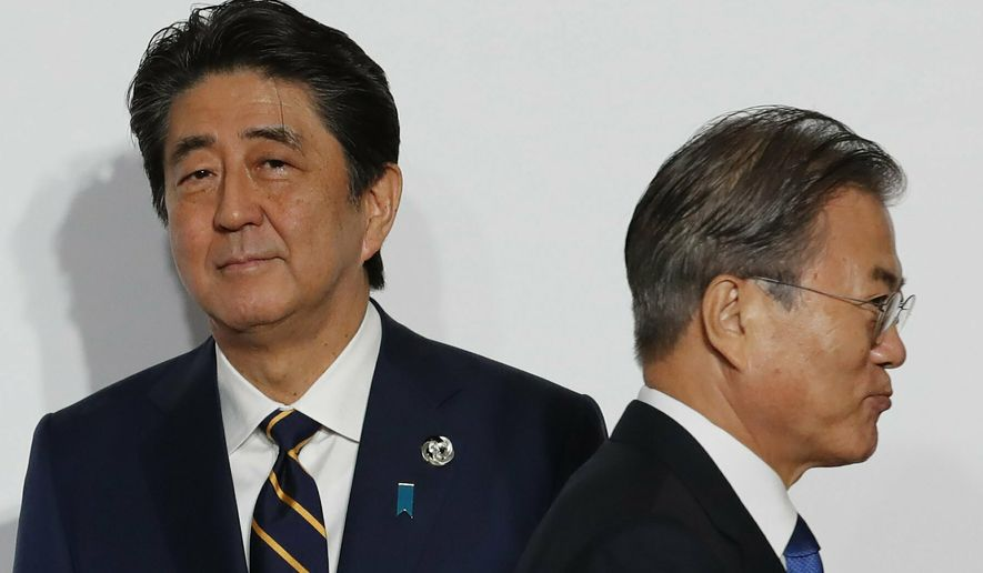 In this June 28, 2019, file photo, South Korean President Moon Jae-in, right, walks by Japanese Prime Minister Shinzo Abe upon his arrival for a welcome and family photo session at the G-20 leaders summit in Osaka, western Japan. South Korea said Thursday, Aug. 22, it is canceling an intelligence-sharing pact with Japan amid a bitter trade dispute, a surprise announcement that is likely to set back U.S. efforts to bolster mutual security cooperation with two of its most important allies in the Asian region. (Kim Kyung-Hoon/Pool Photo via AP, File)
