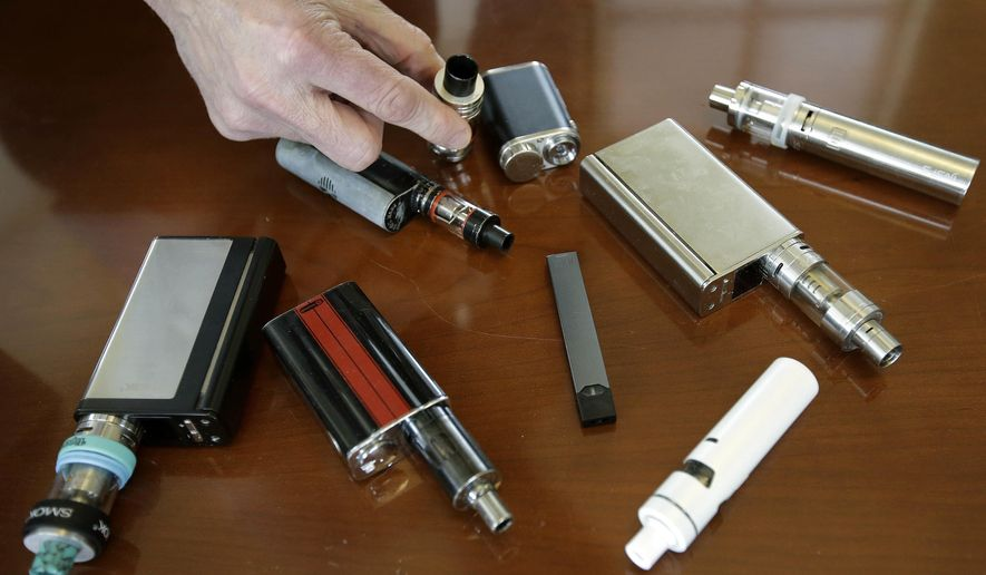 """In this Tuesday, April 10, 2018 photo, Marshfield High School Principal Robert Keuther displays vaping devices that were confiscated from students in such places as restrooms or hallways at the school in Marshfield, Mass. Illinois health officials are reporting what could be United States' first death tied to vaping. In a Friday, Aug. 23, 2019, news release, the Illinois Department of Public Health says a person who recently vaped died after being hospitalized with """"severe respiratory illness."""" The agency didn't give any other information about the patient, including a name or where the person lived. (AP Photo/Steven Senne, File)"""