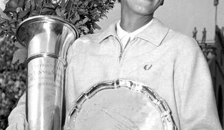 FILE - In this Sept. 9, 1957, file photo, Althea Gibson smiles as she holds her trophies she won by capturing the National women's singles tennis championship at the West Side Tennis Club in Forest Hills, N.Y. Gibson won an amazing 11 Grand Slam titles in three years from 1956-58, including the French Open, Wimbledon and U.S. Open. On Monday, Aug. 26, 2019, the USTA will unveil a statue in her honor at the U.S. Open. (AP Photo, File)