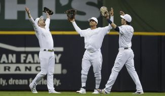 Milwaukee Brewers' Ryan Braun, Trent Grisham and Christian Yelich celebrate after a baseball game against the Arizona Diamondbacks Friday, Aug. 23, 2019, in Milwaukee. The Brewers won 6-1. (AP Photo/Morry Gash)