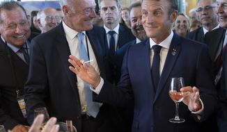 French President Emmanuel Macron, right right, flanked by President of the Nouvelle-Aquitaine region Alain Rousset, center, samples local produce and wine, as he tours the exhibition hall above the international press center on the opening day of the G7 summit, in Anglet, southwestern France, Saturday Aug.24, 2019. U.S. President Donald Trump and the six other leaders of the Group of Seven nations will begin meeting Saturday for three days in the southwestern French resort town of Biarritz. France holds the 2019 presidency of the G-7, which also includes Britain, Canada, Germany, Italy and Japan. Biarritz. (Ian Langsdon, Pool via AP)