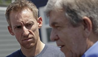 FILE--In this July 26, 2019, file photo, Jason Kander, left, listens while Missouri Republican Sen. Roy Blunt talks to the media after touring the Veteran's Community Project in Kansas City, Mo. Kander's job running a nonprofit for homeless veterans has made the Kansas City site a campaign stop for Democratic presidential hopefuls. The former Missouri secretary of state was considered a strong candidate to be mayor of Kansas City. Then he dropped out of the race to get treatment for the post-traumatic stress disorder he'd struggled with since leaving the Army 11 years earlier. (AP Photo/Charlie Riedel, File)