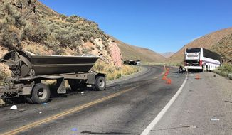 This photo released by the Nevada Highway Patrol shows the scene of a fatal accident involving a coach bus  and a tractor-trailer rig Saturday, Aug. 24, 2019 on State Route 766 approximately 6 miles north of Carlin, Nev.  The bus carrying mine employees collided head-on with the tractor-trailer rig causing the fatalities and several injuries authorities said.  (Jim Stewart/Nevada Highway Patrol via AP)