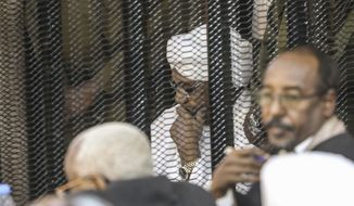 Sudan's autocratic former President Omar al-Bashir sits in a cage during his trial on corruption and money laundering charges in Khartoum, Sudan, Saturday, Aug. 24, 2019. (AP Photo)