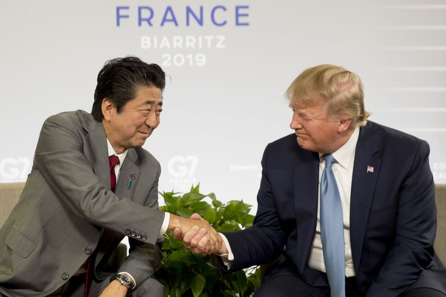 U.S President Donald Trump and Japanese Prime Minister Shinzo Abe shake hands as they participate in a bilateral meeting at the G-7 summit in Biarritz, France, Sunday, Aug. 25, 2019. (AP Photo/Andrew Harnik)