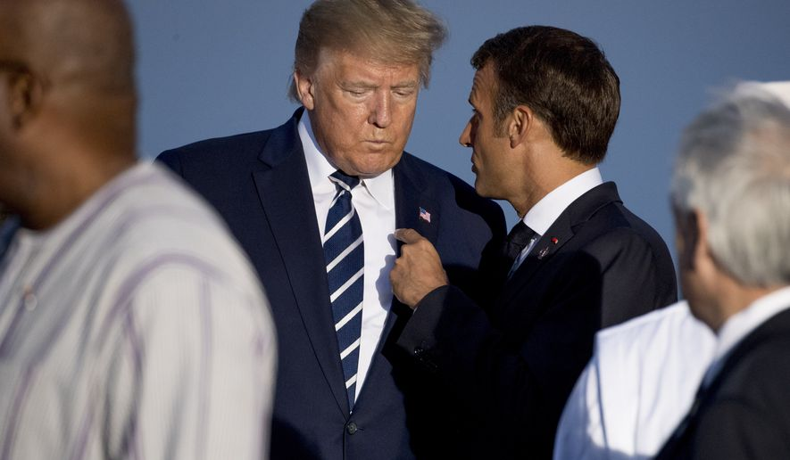 President Donald Trump and French President Emmanuel Macron, right, speak together following the G-7 family photo at G-7 summit at the Hotel du Palais in Biarritz, France, Sunday, Aug. 25, 2019. (AP Photo/Andrew Harnik)