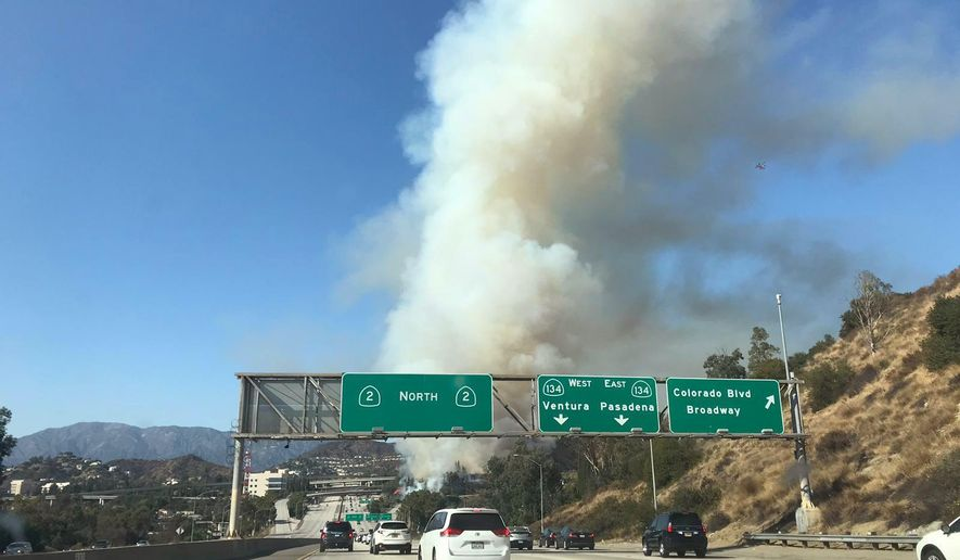 Traffic slows down as a wildfire burns on the north side of CA-134 and CA-2 freeways, slowly backing towards homes in Glendale, Calif., Sunday, Aug. 25, 2019. The brush fire erupted near the border of Glendale and Eagle Rock and shut down the 134 Freeway in both directions, according to the Glendale Fire Department. (Lucas Dovarganes via AP)