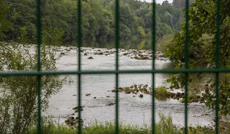 In this photo taken Friday, Aug. 23, the Kupa river on the Slovenia-Croatia border is seen through the border fence in the village of Preloka, Slovenia. Police in Croatia say a migrant has died after a van carrying 12 of them plunged into a river near the border with Slovenia, early Sunday. Slovenia started erecting additional fences on its southern border with Croatia after a considerable increase in the number of migrants trying to illegally cross between the two European Union-member states. (AP Photo/Darko Bandic)