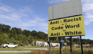 FILE - In this Oct. 16, 2013 file photo, motorists drive past a newly installed billboard near the intersection of Arkmo Road and Vine Road in Harrison, Ark. The threat of white supremacy has been well known in Arkansas, where various extremist groups have made their home over the decades, but efforts to enact a hate crimes measure have been unsuccessful. The latest push comes from Republican Gov. Asa Hutchinson. (Samantha Baker/The Arkansas Democrat-Gazette via AP)
