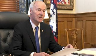 FILE - In this April 10, 2019 file photo, Arkansas Gov. Asa Hutchinson speaks to reporters in his office at the state Capitol in Little Rock, Ark. Hutchinson says the state should have harsher penalties for people convicted of targeting others because of their race, ethnicity or religion, calling for the measure in the wake of two mass shootings that include one in Texas being investigated as a hate crime by federal authorities. (AP Photo/Andrew DeMillo, File)