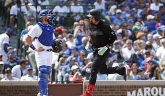 Washington Nationals' Anthony Rendon, right, crosses home plate past Chicago Cubs' catcher Jonathan Lucroy, left, after hitting a solo home run off of Chicago Cubs' Cole Hamels during the fourth inning of a baseball game, Sunday, Aug. 25, 2019, in Chicago. (AP Photo/Kamil Krzaczynski)