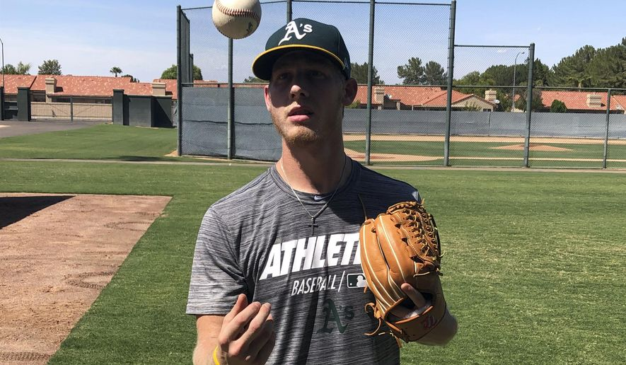 In this Friday, Aug. 23, 2019, photo, Oakland Athletics rookie pitcher Nathan Patterson tosses a baseball, in Mesa, Ariz. Patterson earned a contract after hitting 96 mph on the radar gun at a fan pitching challenge at Colorado's Coors Field. He made his last appearance for the A's in rookie league on Aug. 25, allowing a hit in 2 2/3 innings with two strikeouts against the Cleveland Indians. (AP Photo/John Marshall)