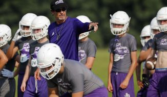 In this Aug. 5, 2019, photo, head coach Art Briles instructs his team during a practice at Mount Vernon High Schoo in Mount Vernon, Texas. Most of the town's residents knew nothing about the possibility of Briles becoming coach until the school board unanimously approved his hiring in a special meeting on the Friday night going into Memorial Day weekend. (AP Photo/Tony Gutierrez)