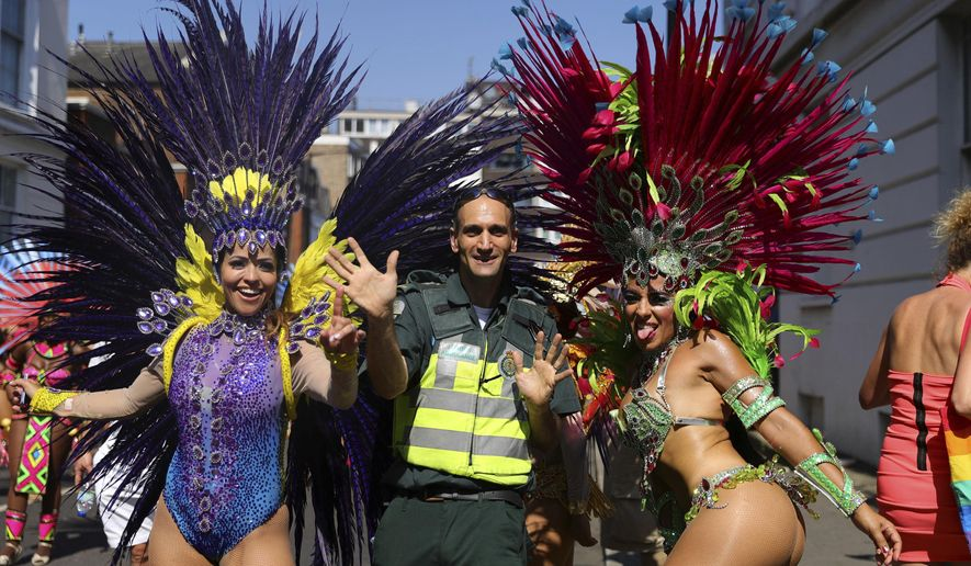 A paramedic joins dancers during the the Notting Hill Carnival in west London, Monday, Aug. 26, 2019. (Aaron Chown/PA via AP)
