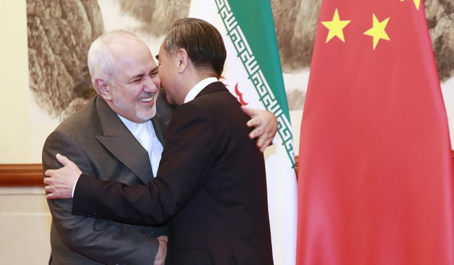 Chinese Foreign Minister Wang Yi, right, shakes hands with Iranian Foreign Minister Mohammad Javad Zarif at the Diaoyutai State Guesthouse in Beijing, Aug. 26, 2019. (How Hwee Young/Pool Photo via AP)