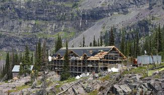 In this Aug. 8, 2019 photo, construction crews continue the rebuilding of the Sperry Chalet dormitory in Glacier National Park, Mont., after it was nearly destroyed by a 2017 fire. Crews work 10-hour shifts, eight days straight before hiking out to take six days off. They hope to complete the work by Oct. 1 so the chalet can be open for visitors next summer. (Casey Kreider/Daily Inter Lake via AP)