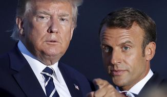 U.S President Donald Trump talks to French President Emmanuel Macron during the G7 family photo Sunday, Aug. 25, 2019 in Biarritz. A top Iranian official paid an unannounced visit Sunday to the G-7 summit and headed straight to the buildings where leaders of the world's major democracies have been debating how to handle the country's nuclear ambitions. (Christian Hartmann, Pool via AP)