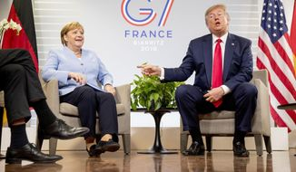 U.S. President Donald Trump, accompanied by German Chancellor Angela Merkel, left, speaks to reporters during a bilateral meeting at the G-7 summit in Biarritz, France, Monday, Aug. 26, 2019. (AP Photo/Andrew Harnik)
